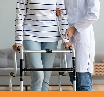 Female patient in blue jeans uses her durable medical equipment with the support of her physical therapist.