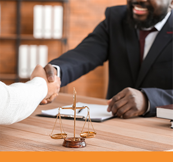 A smiling African-American lawyer shakes hands with a client across a wood table with the scales of justice nearby.