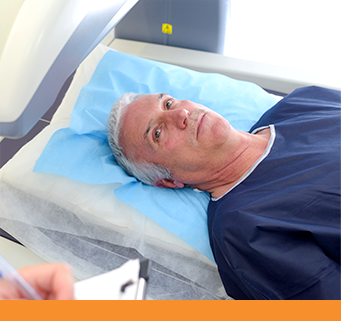A senior male patient lays in an open MRI machine and looks up at the tech for directions.