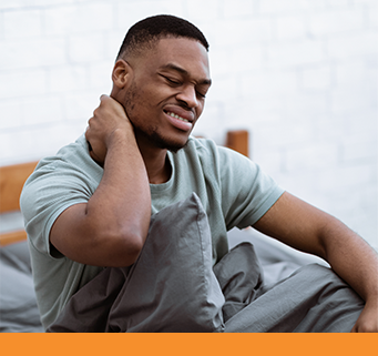 Young African-American male winces in pain and grabs the side of his neck while sitting up in bed.