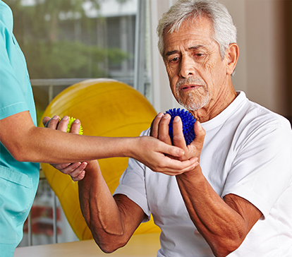 Older male patient in white t-shirt squeezes a blue ball in his left hand and a yellow ball in his right hand