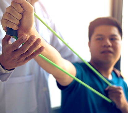 Young patient uses green resistance band with instruction from his physical therapist