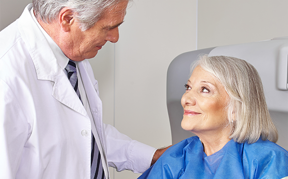 An older male doctor reassures a female senior patient about her open MRI procedure.