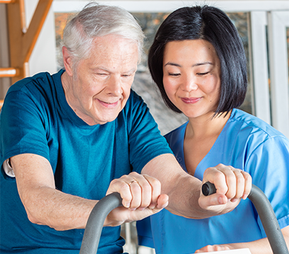Asian physical therapist works with senior patient to exercise on a stationary bicycle.