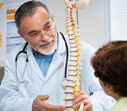 Older physician with beard shows a model of the spine to young physicians patient