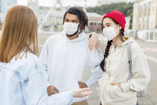 A young couple take COVID-19 precautions and are wearing face masks while visiting outdoors with a young female friend.