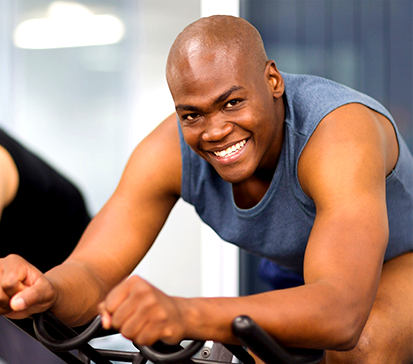 Young African American male works out at The Spine Center on a spin bicycle