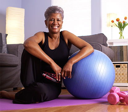 African American lady with total hip replacement exercises at home with purple exercise ball