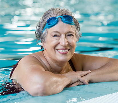 Senior Caucasian woman with blue goggles practices aqua therapy at The Spine Center