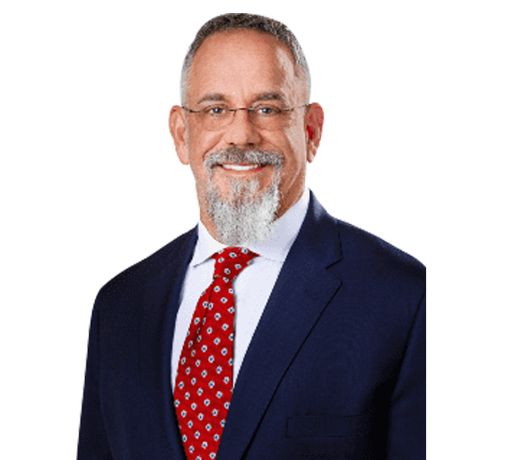 Headshot of Physician Kyle Coffee in blue suit and red tie smiling at camera on transparent background