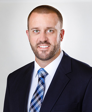 Headshot of Physicians Assistant Jacob Nelson in suit smiling at camera on transparent background